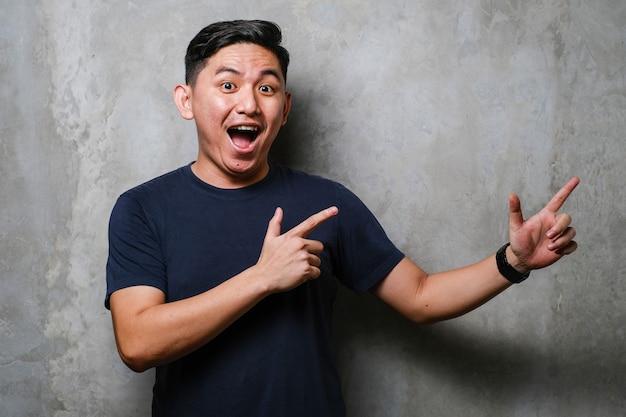 笑顔とカメラを両手と指で横に向けて見ている未完成のコンクリートの壁の背景の上の若いハンサムなアジア人男性。