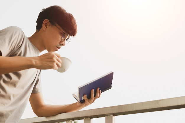 Young handsome asian man reading book and drinking tea at room balcony in free time from working at home, knowledge and learning concept