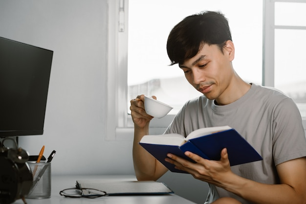 Young handsome asian man reading book and drinking tea at work desk in free time from working at home, knowledge and learning concept