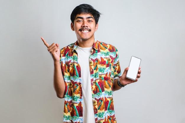 白い孤立した背景の上のスマートフォンの空白の画面を示す若いハンサムなアジア人は、手と指で横に指して非常に幸せです