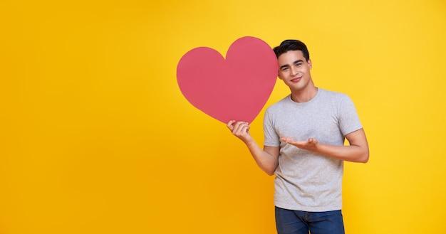 Молодой красивый азиатский мужчина показывает красный знак сердца на желтом. концепция любви и счастливого валентина.