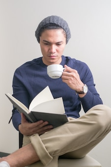 Young handsome asian man sitting while reading book and drinking coffee