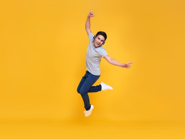 黄色の背景で隔離の音楽を聴いてワイヤレスヘッドフォンを着て笑顔とジャンプの若いハンサムなアジア人男性。