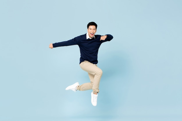 Young handsome asian man smiling and jumping in mid-air on light blue wall