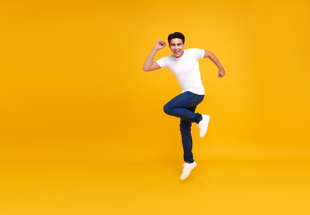 Young handsome asian man smiling and jumping while celebrating success isolated on yellow.
