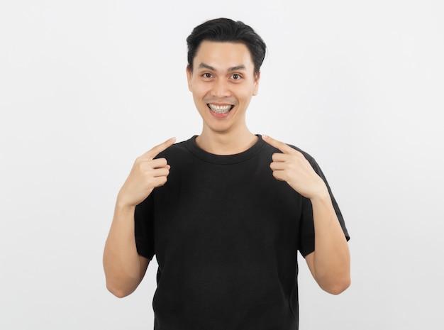 Молодой красивый азиатский человек усмехаясь с расчалками и смотря камеру с изолированный указывать пальца