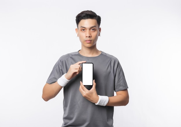 Young handsome asian man in sport outfits showing phone with blank screen and listening music isolated