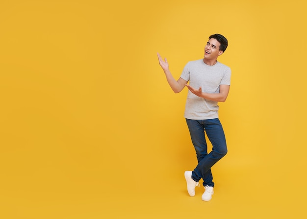 Young handsome asian man standing with his finger pointing isolated on yellow background with copy space. panoramic background. Premium Photo