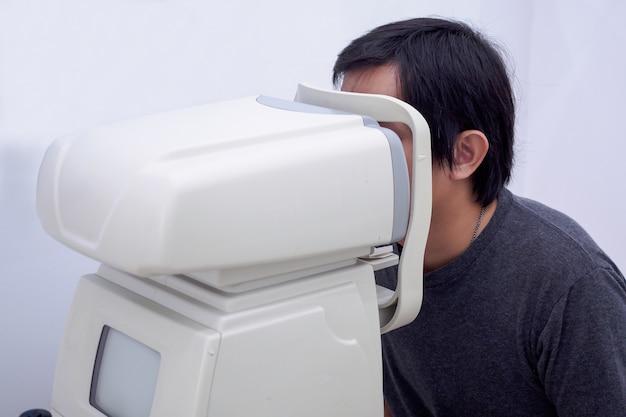 若いハンサムなアジアの男性は、光学目試験機で視力検査を受けます