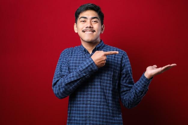 빨간색 배경 위에 캐주얼한 플란넬 셔츠를 입은 젊은 미남 아시아 남성은 손으로 발표하고 손가락으로 가리키며 놀라고 카메라를 향해 미소를 지었습니다. 프리미엄 사진