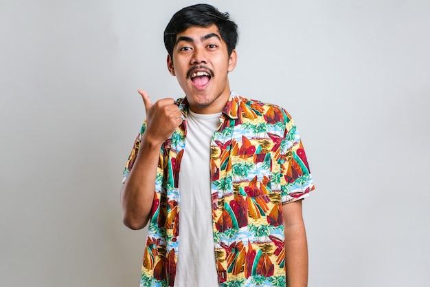 顔に大きな笑顔で白い背景の上にカジュアルなシャツを着ている若いハンサムなアジア人男性。カメラを見ている側に手指で指しています。