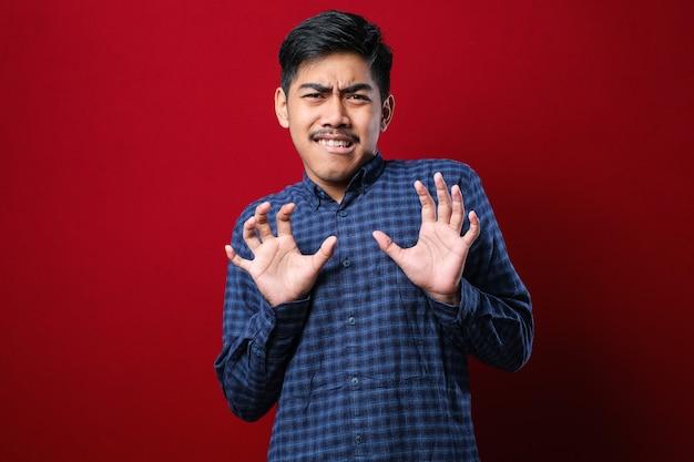 빨간색 배경 위에 서 있는 캐주얼 셔츠를 입은 젊고 잘생긴 아시아 남자는 두렵고 역겨운 표정으로 거부와 거부를 보여주는 손바닥을 움직입니다. 중지 및 금지.