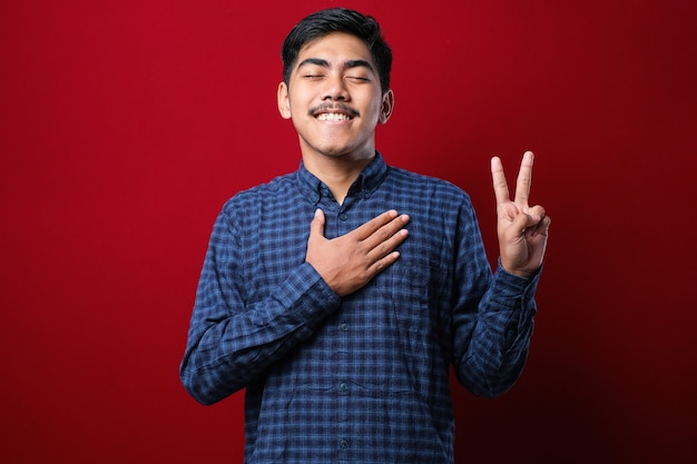 赤い背景の上に立ってカジュアルなシャツを着た若いハンサムなアジア人男性が胸に手を当てて指を上げて誓い、忠誠の誓いを立てる