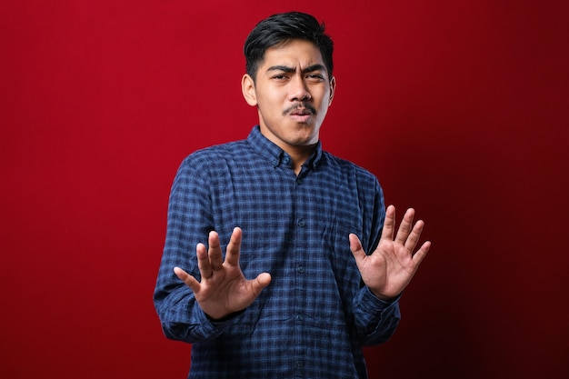 Young handsome asian man wearing casual shirt standing over red background moving away hands palms showing refusal and denial with afraid and disgusting expression. stop and forbidden.