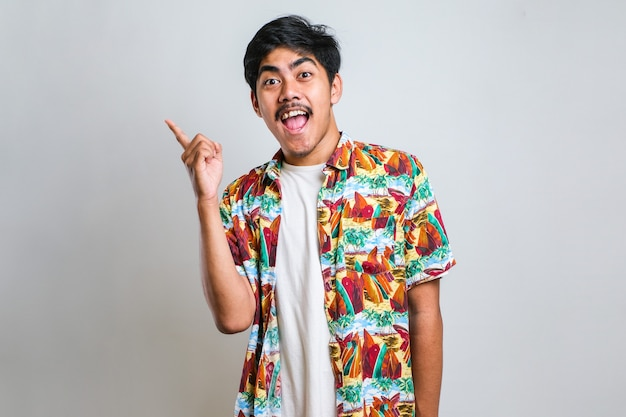 Young handsome asian man wearing casual shirt over white background with a big smile on face; pointing with hand finger to the side looking at the camera.