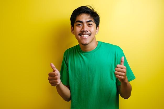 緑のtシャツを着て、孤立した黄色の背景の上に立って幸せな親指を手でジェスチャーをしている若いハンサムなアジア人男性。成功を示しているカメラを見て表現を承認します。