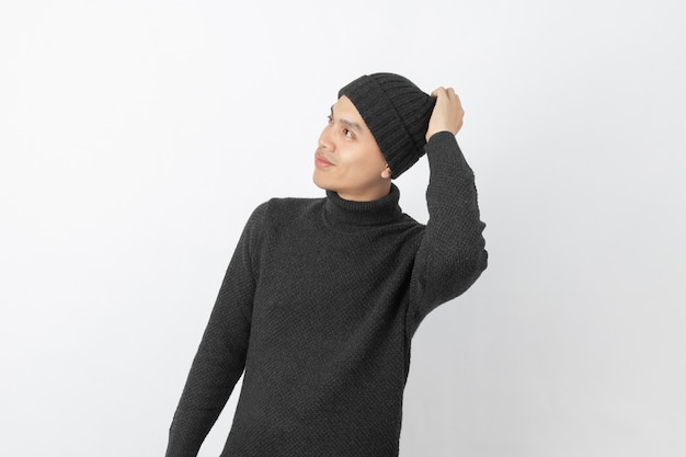 Young handsome asian man wearing grey sweater and beanie thinking an idea while looking up