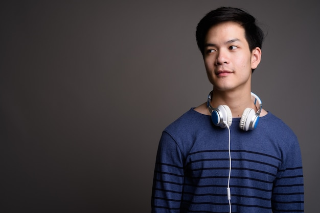 Young handsome asian man wearing headphones on gray