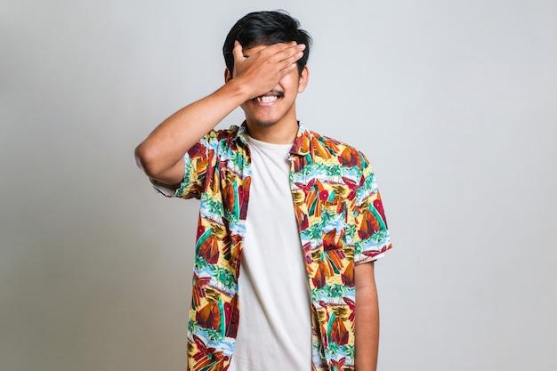 片方の目を手で覆う白い孤立した背景の上に立っている白いビーチシャツを着て、顔に自信を持って笑顔と驚きの感情を身に着けている若いハンサムなアジア人男性。