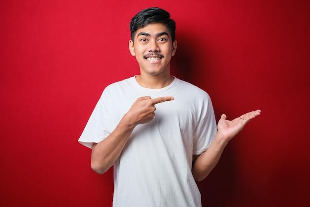 빨간 배경 위에 흰색 티셔츠를 입은 젊고 잘생긴 아시아 남자는 손으로 발표하고 손가락으로 가리키며 놀라고 카메라를 향해 미소를 지었습니다.