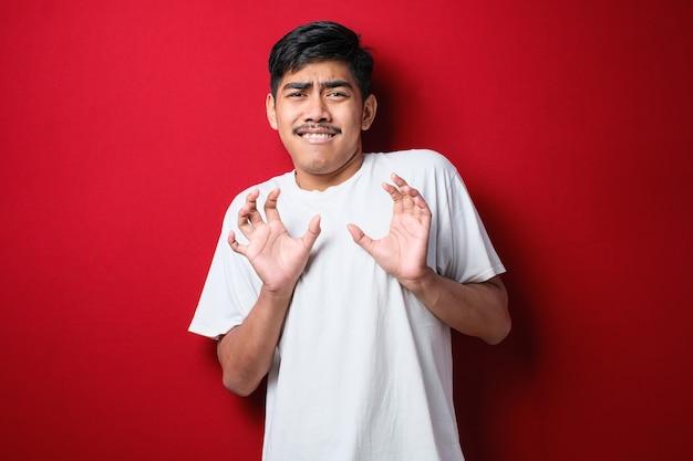 빨간색 배경 위에 서 있는 흰색 티셔츠를 입은 젊고 잘생긴 아시아 남성은 두렵고 역겨운 표정으로 거부와 거부를 보여주는 손바닥을 멀리 움직입니다. 중지 및 금지.