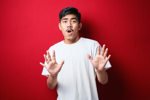빨간색 배경 위에 서 있는 흰색 티셔츠를 입은 젊고 잘생긴 아시아 남자는 두렵고 역겨운 표정으로 거부와 거부를 보여주는 손바닥을 멀리 움직입니다. 중지 및 금지.
