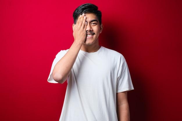 흰색 티셔츠를 입은 젊고 잘생긴 아시아 남자는 한쪽 눈을 손으로 덮고 얼굴에 자신감 넘치는 미소를 짓고 놀라움을 주는 붉은 외진 배경 위에 서 있습니다.