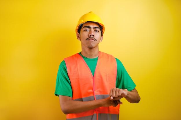 Молодой красивый азиатский рабочий мужчина в оранжевом жилете и шлеме безопасности спешит, указывая на время просмотра, нетерпеливо, расстроенный и сердитый за задержку крайнего срока