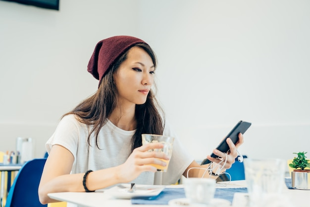 Молодая красивая азиатская женщина сидит в баре