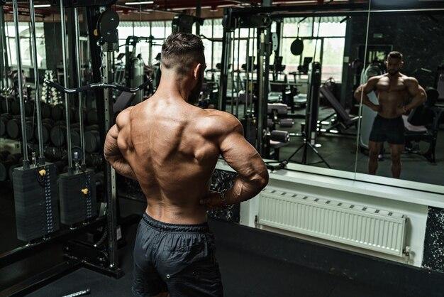 若いハンサムなアスリート、ボディービルダー、完璧なボディの重量挙げ、ジム、腹部の筋肉、上腕二頭筋、上腕三頭筋でワークアウト。裸の胴体。
