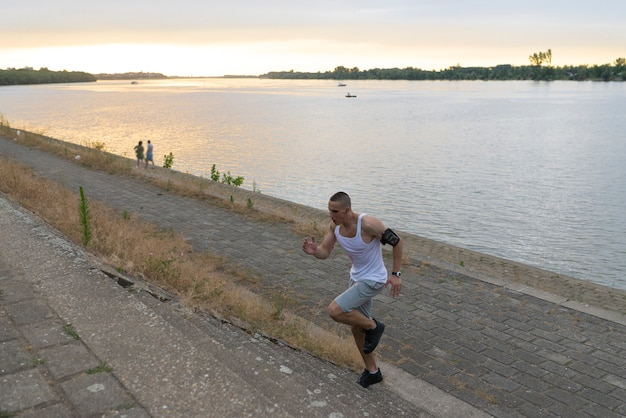 Young handsome athlete running upstairs by the river bank