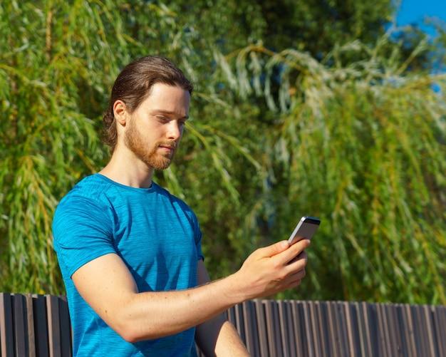 공원에서 운동하는 동안 현대 스마트폰에서 피트니스 앱을 사용하는 젊고 잘 생긴 운동 남자