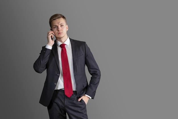 電話で話しているスーツと赤いネクタイの若いハンサムで魅力的なブロンドの男 Premium写真