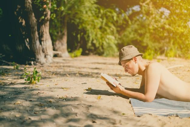 Молодой красивый привлекательный человек в панаме лежа на песчаном пляже рая и читая книгу в летний день