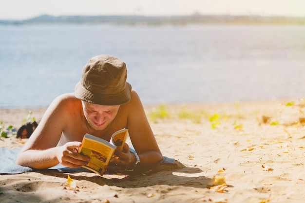 Young handsome attractive man in panama lying on sandy heaven beach and reading a book on a summer day