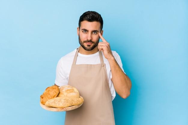 Молодой красивый пекарь изолировал указывая висок пальцем, думая, сосредоточенный на задаче.
