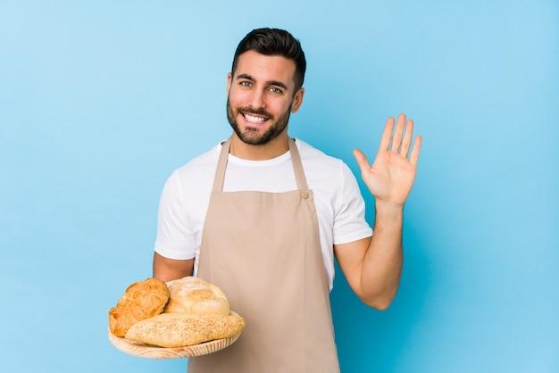 若いハンサムなパン屋の男は指で陽気な表示数5を笑顔を分離しました。