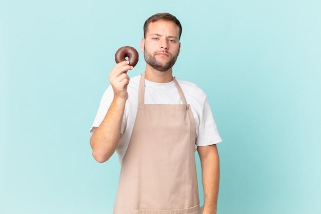 Молодой красивый пекарь с пончиком