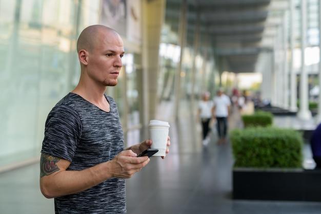 Молодой красивый лысый мужчина держит бумажную кофейную чашку и мобильный телефон
