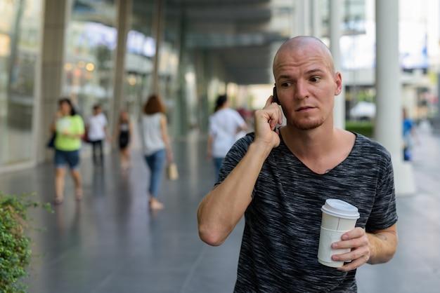 Молодой красивый лысый мужчина держит бумажную кофейную чашку во время разговора по телефону
