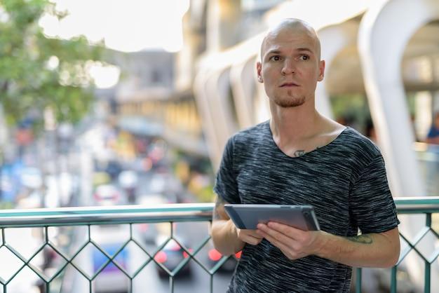 Молодой красивый лысый мужчина думает, держа цифровой планшет
