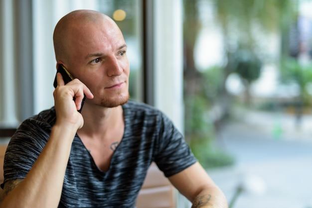 Молодой красивый лысый мужчина думает во время разговора по мобильному телефону