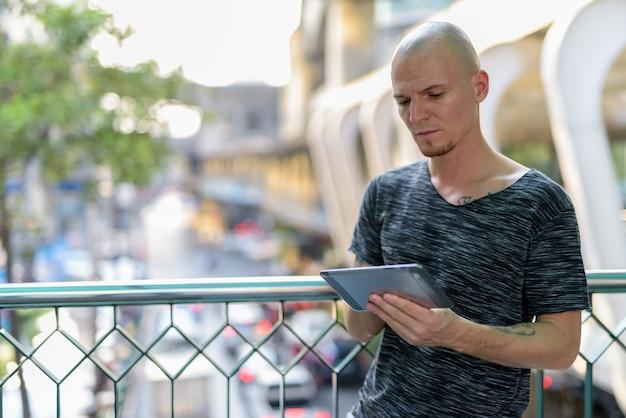 Молодой красивый лысый мужчина с помощью цифрового планшета на пешеходном мосту