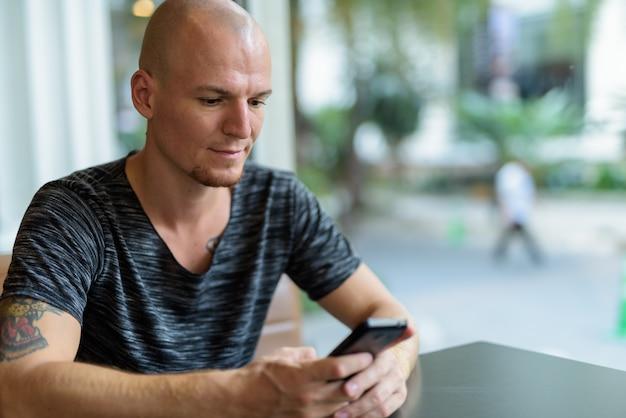 Молодой красивый лысый мужчина с помощью мобильного телефона в ресторане