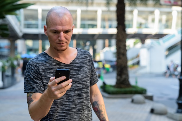 Молодой красивый лысый мужчина с помощью мобильного телефона возле торгового центра на улице