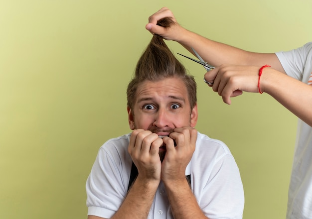 Young handsome barber biting his fingers scared about getting all his hair cut off isolated on olive green background with copy space