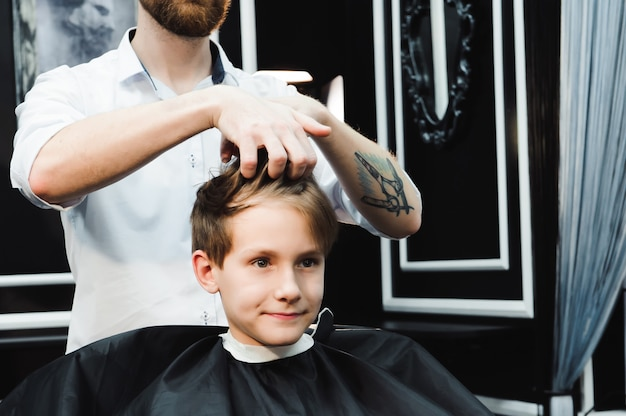 Young handsome barber making haircut of boy in barbershop