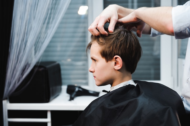 Young handsome barber making haircut of cute boy in barbershop