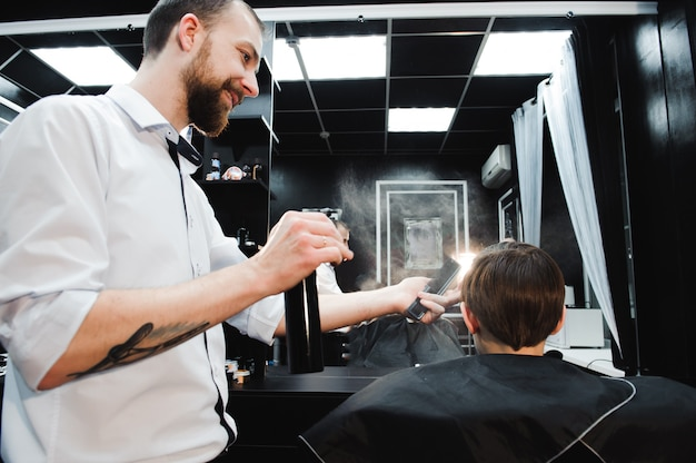 Young handsome barber making haircut of cute boy in barbershop.