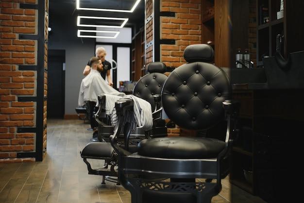 理髪店で魅力的なひげを生やした男のヘアカットを作る若いハンサムな理髪店